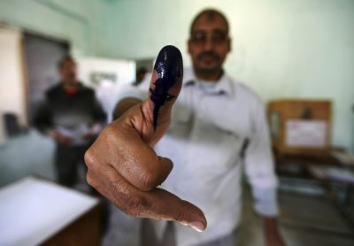 A man shows his ink stained finger after casting his vote at a polling station during parliamentary elections in Cairo