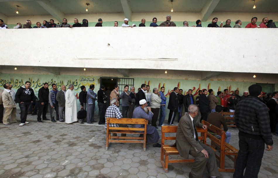People queue at a polling station as they wait to cast their votes during parliamentary elections in Cairo