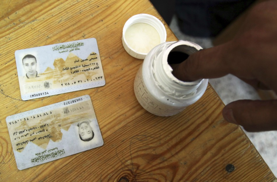 A man dips his finger in ink after casting a vote at a polling station during a parliamentary election in Cairo