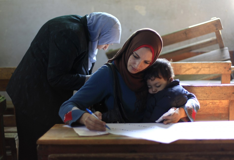 An Egyptian woman reads a ballot paper before casting her vote at a polling station during the parliamentary election in Cairo