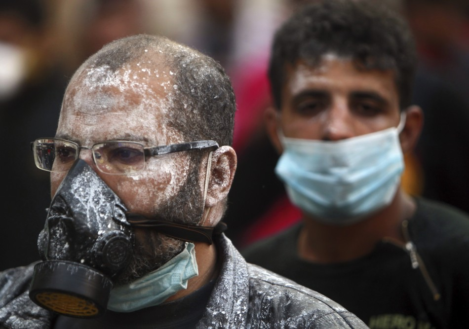 Protesters, with medical cream applied to their faces to protect against tear gas, wear surgical and gas masks during clashes near Tahrir Square