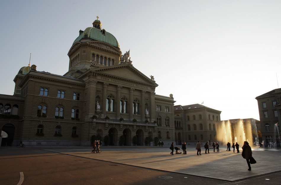 People walk around the Swiss Federal Palace (Bundeshaus) in Bern