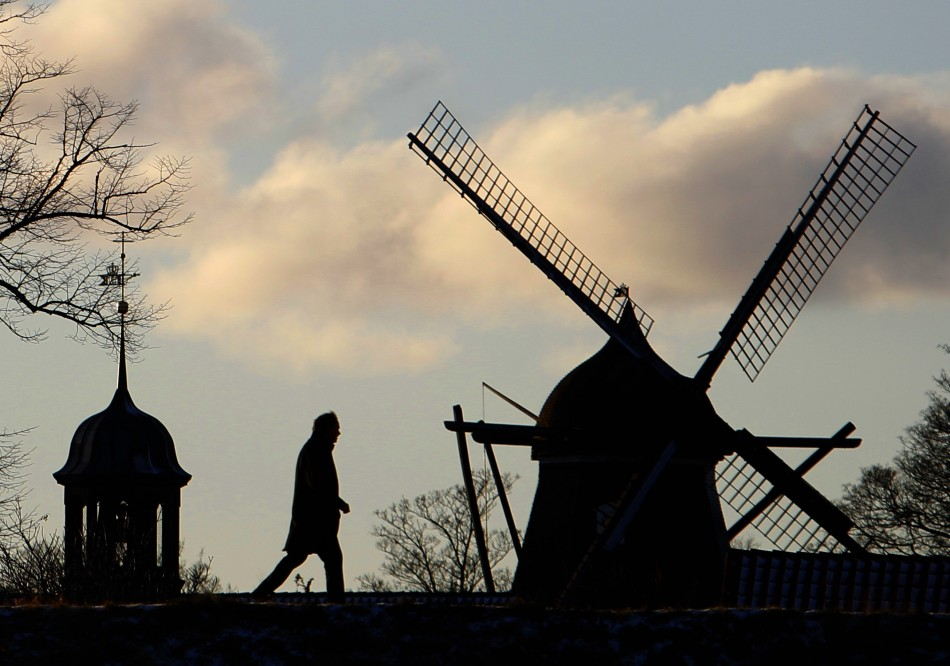 A man walks past a windmill in Kastellet park in Copenhagen