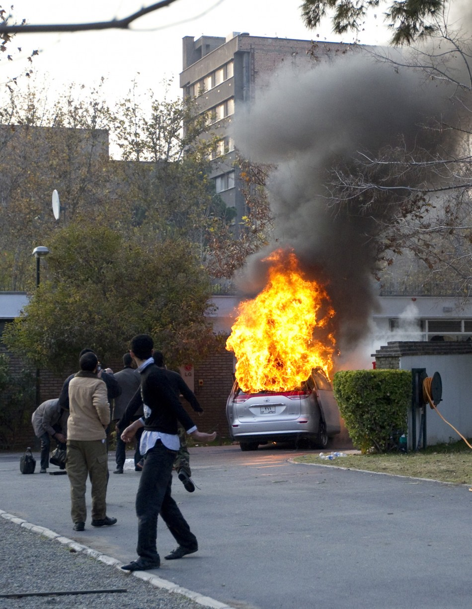Protesters walk in the British embassy as an embassy car burns in Tehran