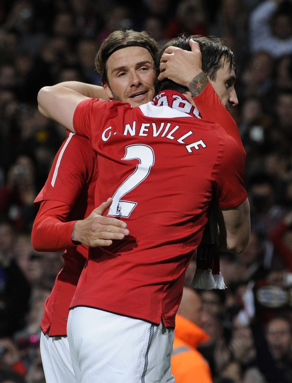 Manchester United's former player Beckham hugs Neville during Neville's testimonial soccer match against Juventus in Manchester