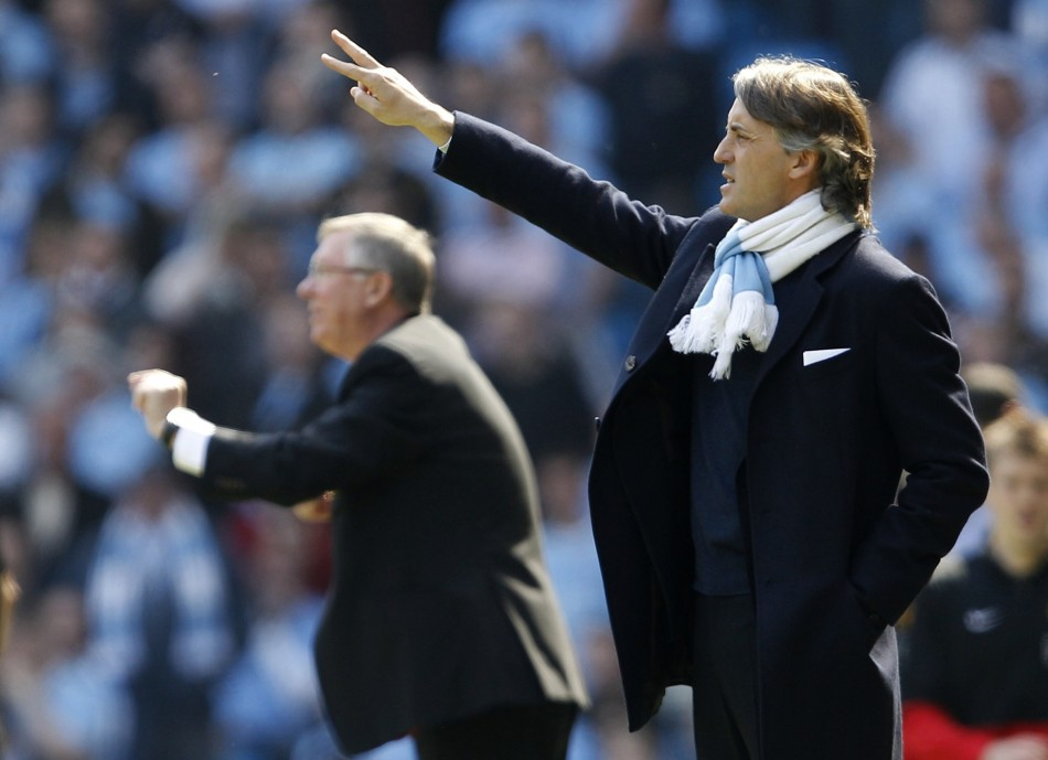 Manchester City's manager Mancini and his Manchester United counterpart Ferguson gesture during their English Premier League soccer match in Manchester