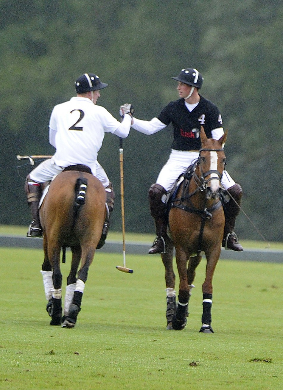 Britains Prince William and Prince Harry shake hands after playing polo against one another during the Sentebale Cup at Coworth park, Berkshire