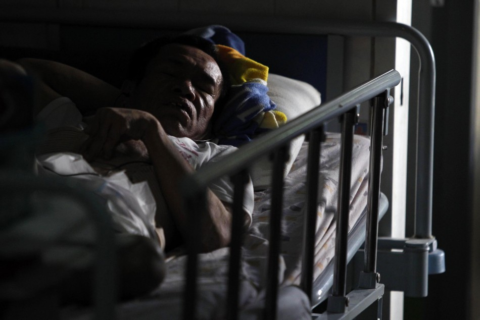 A terminally ill man rests on a bed at a hospice for those dying from AIDS, at Wat Prabat Nampu Buddhist temple in Lopburi province on World AIDS day