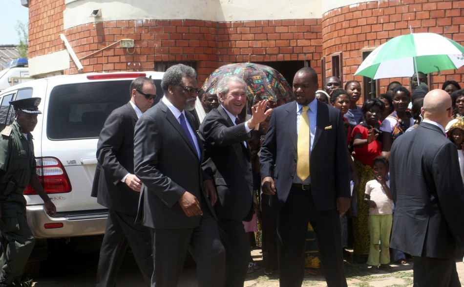 Former US President George Bush (c) flanked by co-director of cervical cancer prevention program Dr Groesbeck Parham (l) and Zambia's Minister for Lusaka Province Miles Sampa (r) waves to mothers at George Clinic where he launched the Red Ribbon Pink Ribb