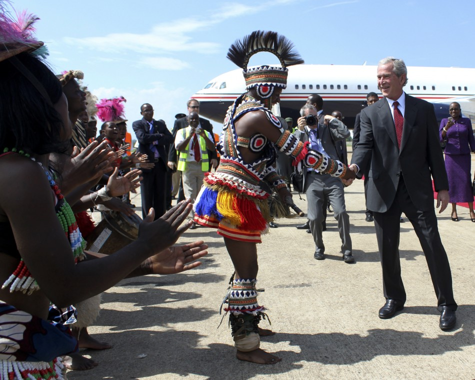 Former U.S. President Bush greets a traditional dancer on arrival at the Kenneth Kaunda International Airport in the capital Lusaka