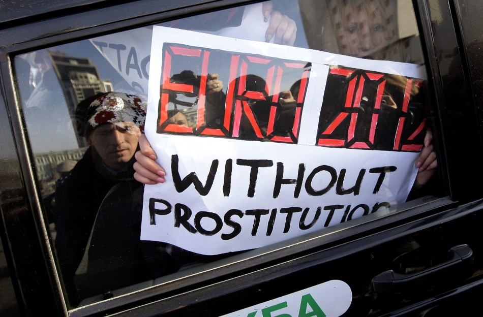 The woman, who only wore briefs and stockings during the protest, held up sexually explicit placards condemning Europes footballs governing body, Uefa.
