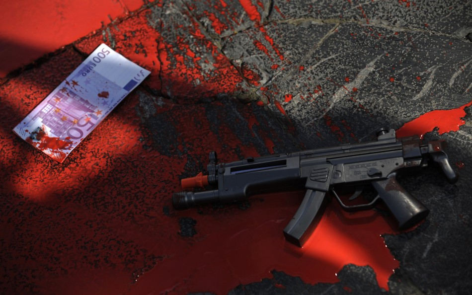 A plastic gun and a fake euro bank note lie in a pool of red paint