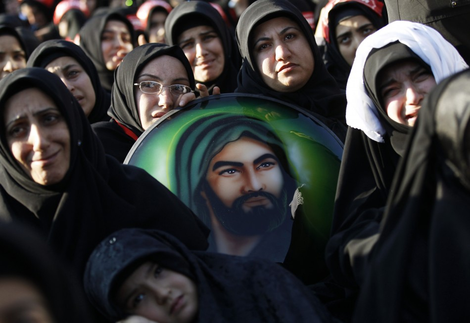 Shiite women holding a portrait of Hazrat Ali, son-in-law of Prophet Mohammad, mourn during an Ashura procession in Istanbul