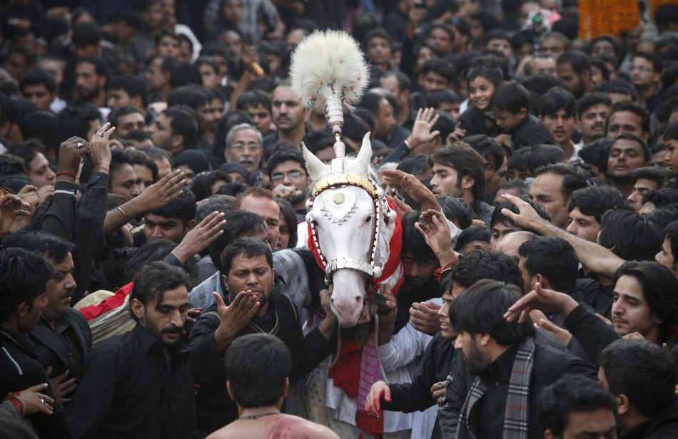 Shiite Muslim men touch a symbolic sacred horse for good luck as they take part in a religious procession ahead of the Ashura festival in Lahore