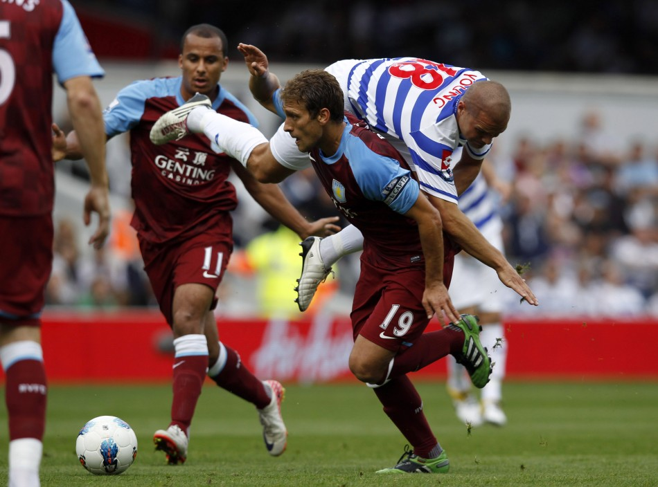 Queens Park Rangers' Luke Young (top) challenges Aston Villa's Stiliyan Petrov