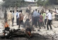Somali police evacuate an injured colleague from the scene of a suicide car bomb near the KM4 building in Hodan district, south of the capital Mogadishu