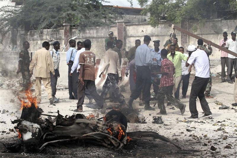 Somali police evacuate an injured colleague from the scene of a car bomb in Somalia.