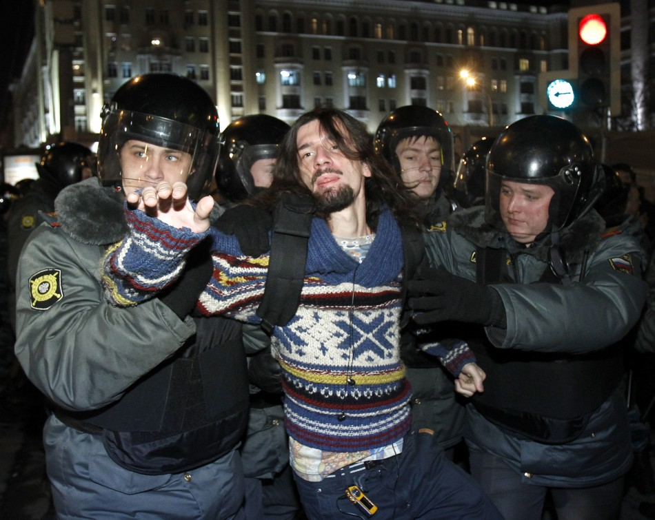 Policemen detain an activist during rally to protest against the results of the parliamentary elections