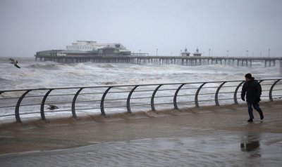 A man braves the wind and rain to walk her dog along the sea front near Blackpool