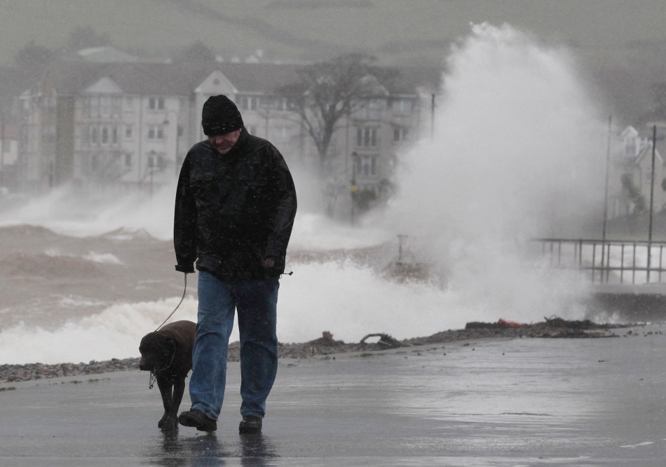 A man walks with his dog along promenade in Largs in west Scotland