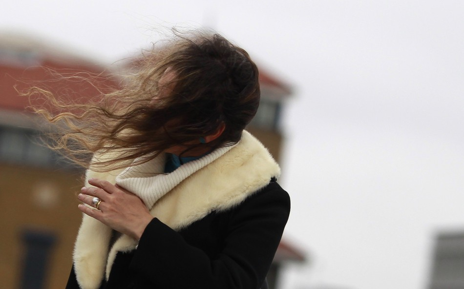 A woman s hair is blown across her face as she walks during a windy day in central London December 8, 2011.