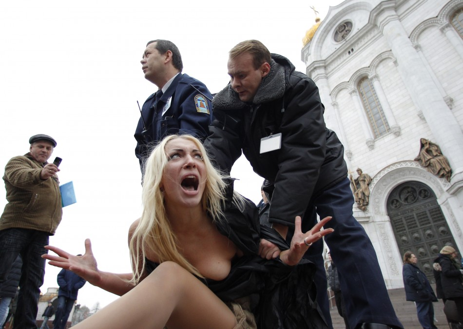 Security guards detain activists from Femen in front of the Cathedral of Christ the Saviour in Moscow Denis