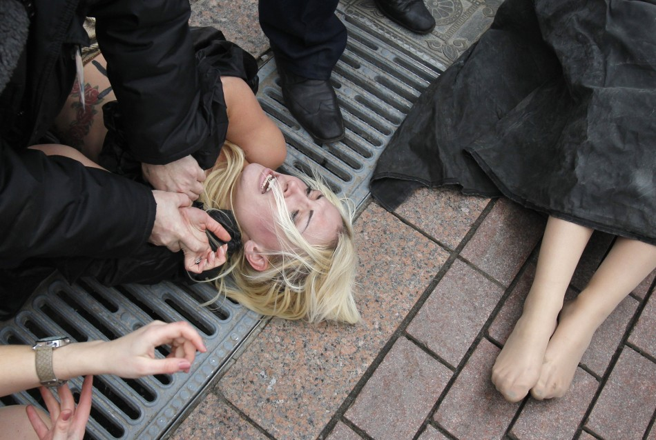 Security guards detain activists from Femen in front of the Cathedral of Christ the Saviour in Moscow