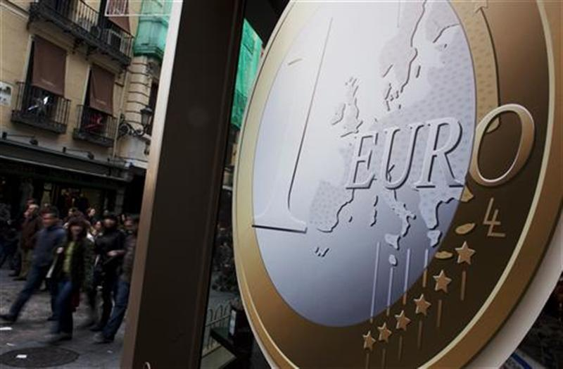 People walk past a pizza shop with a sign of a euro coin used to advertise its prices in central Madrid