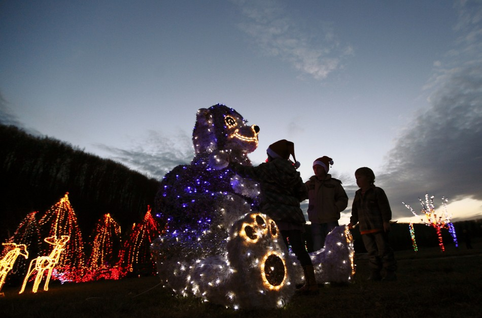 Children play with a decorative bear at a country house estate in the village of Grabovnica near Cazma