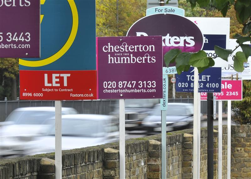 Cars pass property sales and letting signs in west London