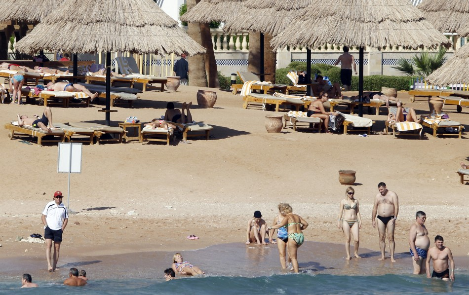 Tourists take a dip in the sea at a beach in the Red Sea resort city of Sharm el-Sheikh