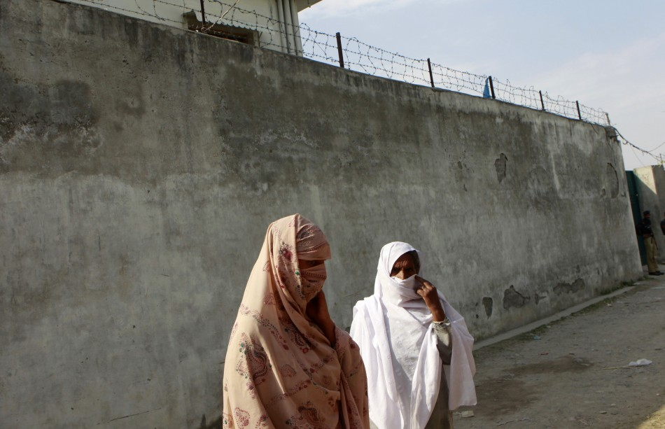 Residents stand outside the compound where al Qaeda leader Osama bin Laden was killed in Abbottabad