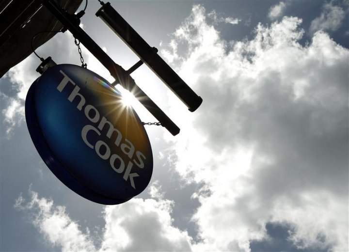 A sign hangs in front of a branch of travel agent Thomas Cook in London