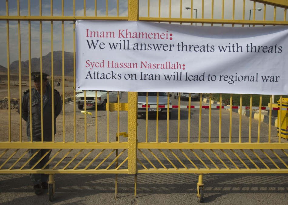 Security officer stands next to banner at the entrance of the Uranium Conversion Facility in Isfahan