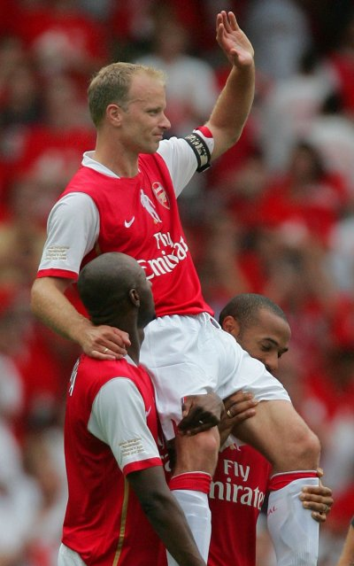Arsenals Bergkamp carried by Viera and Henry at the Emirates Stadium after Arsenals friendly match against Ajax