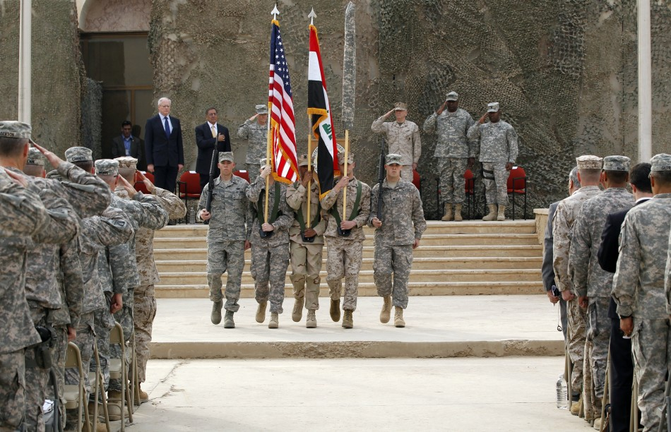 U.S. soldiers carry Iraqi national flag and U.S. flag during ceremony to retire flags, marking end of the U.S. military engagement at Baghdad Diplomatic Support Center