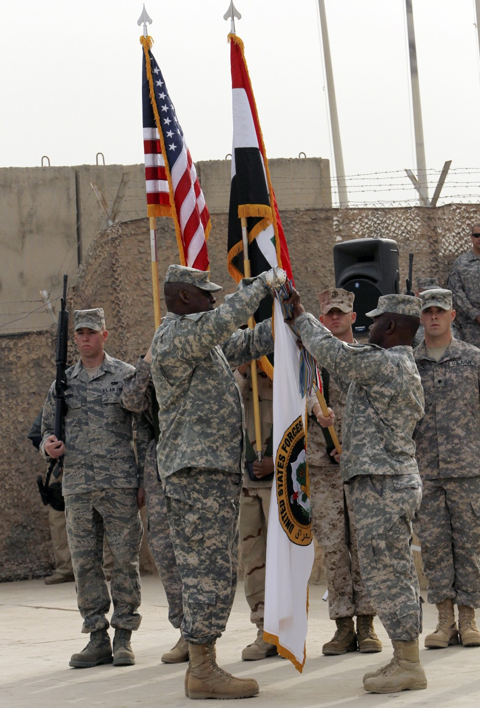 Members of the U.S. military retire its ceremonial flags signifying the end of their presence in Iraq at the Baghdad Diplomatic Support Center