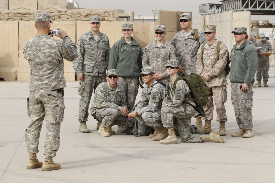 US military personnel pose for a picture before the start of a ceremony marking the end of the U.S. military engagement, at the former US Sather Air Base