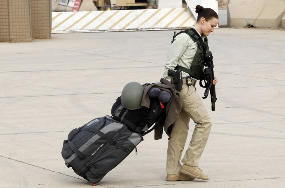 A member of U.S. security personnel pulls her luggage while waiting to depart from Iraq, at the former U.S. Sather Air Base near Baghdad