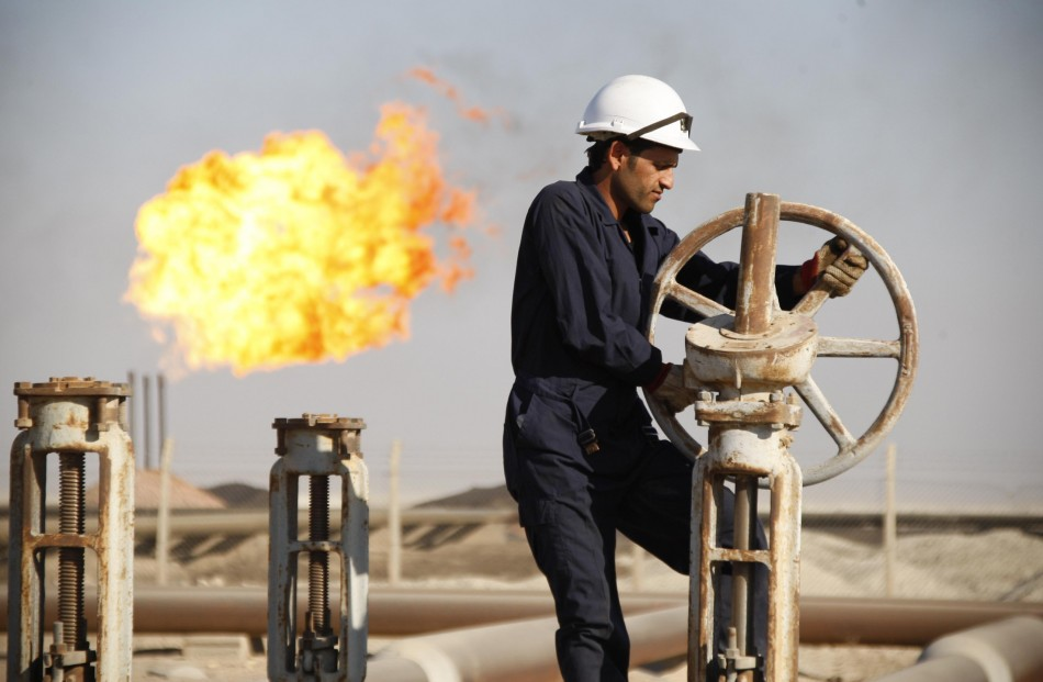 A worker adjusts the valve of an oil pipe at West Qurna oilfield in Iraq's southern province of Basra November 28, 2010
