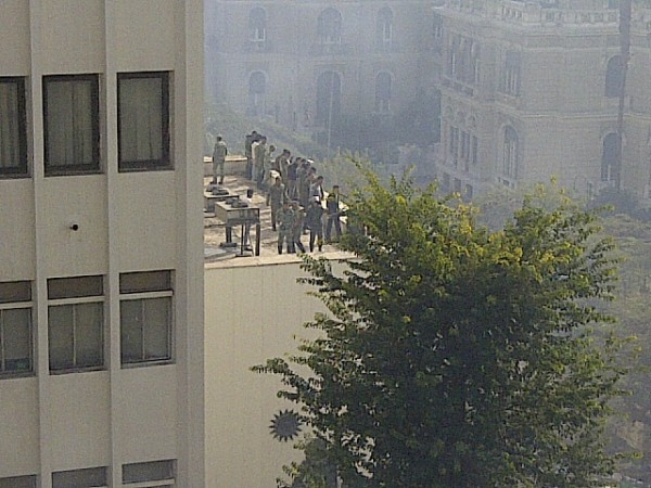 The Egyptians security forces overlooking protesters from the top of the parliament's building