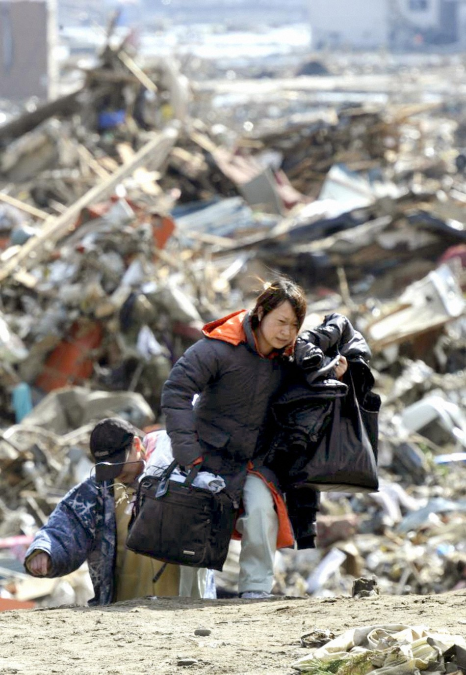 A woman carries her belongings away from her tsunami-stricken home
