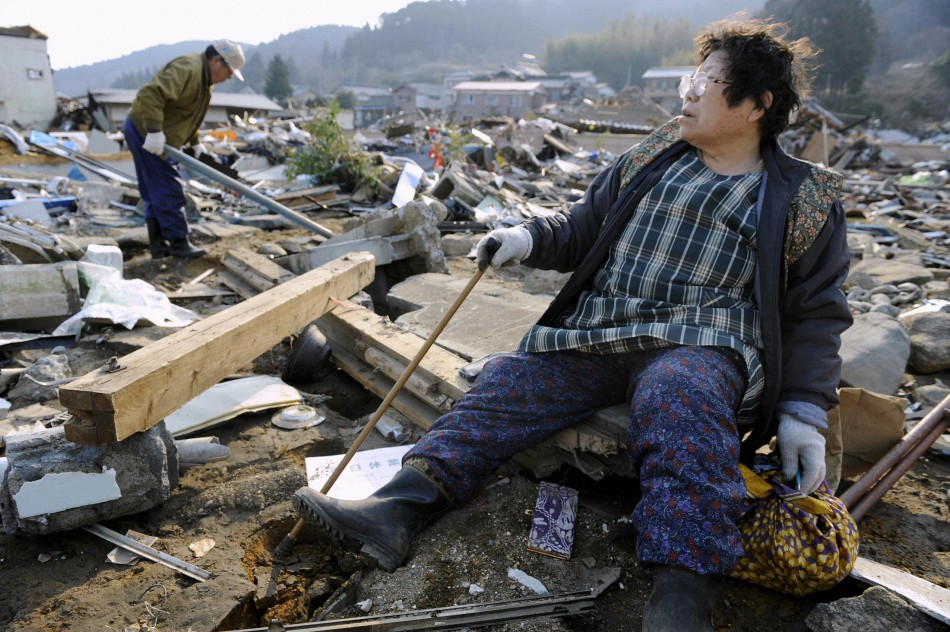 A woman looks out over the destroyed landscape in Ofunato City