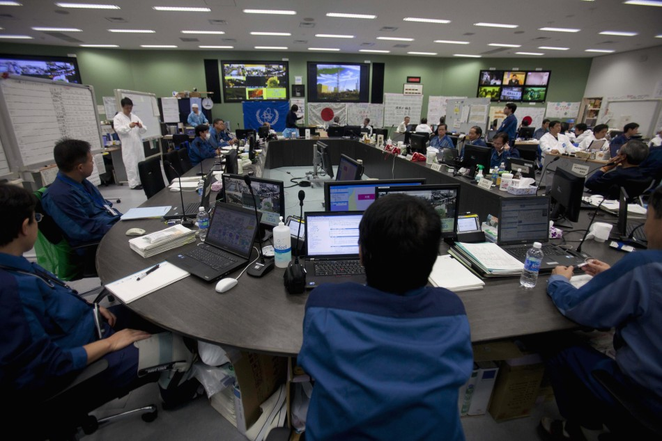Employees of Tokyo Electric Power Co. (TEPCO) work inside the emergency operation