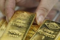 An employee picks up a gold bar at the Austrian Gold and Silver Separating Plant 'Oegussa' in Vienna August 26, 2011.