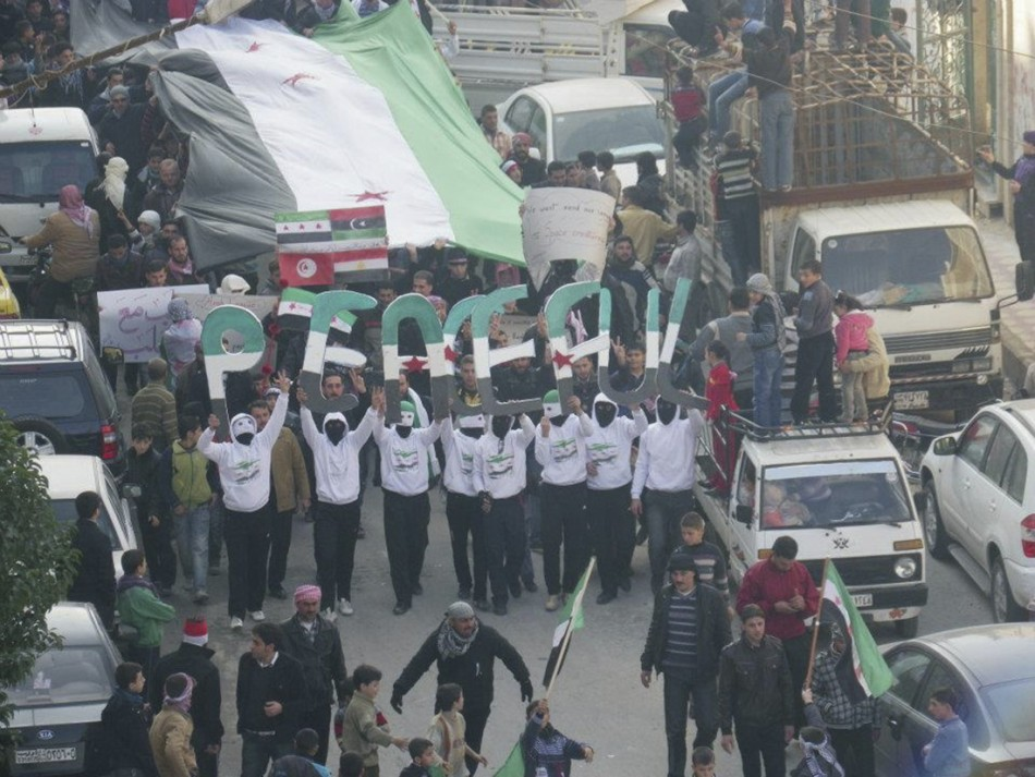 Demonstrators protesting against Syria's President Bashar al-Assad march through the streets after Friday prayers in Adlb