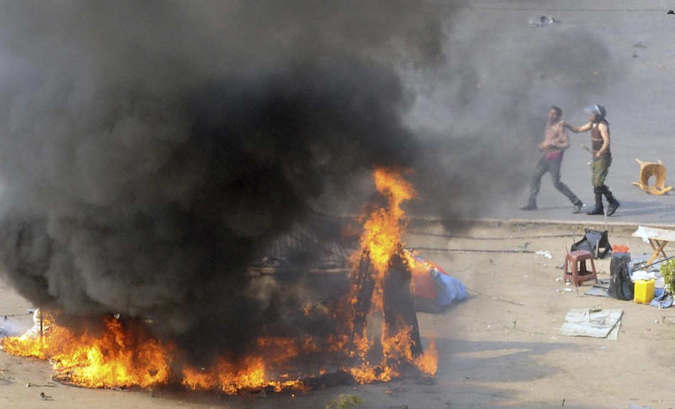 An Egyptian army soldier (R) arrests a protester near a burning tent during clashes at Tahrir Square in Cairo