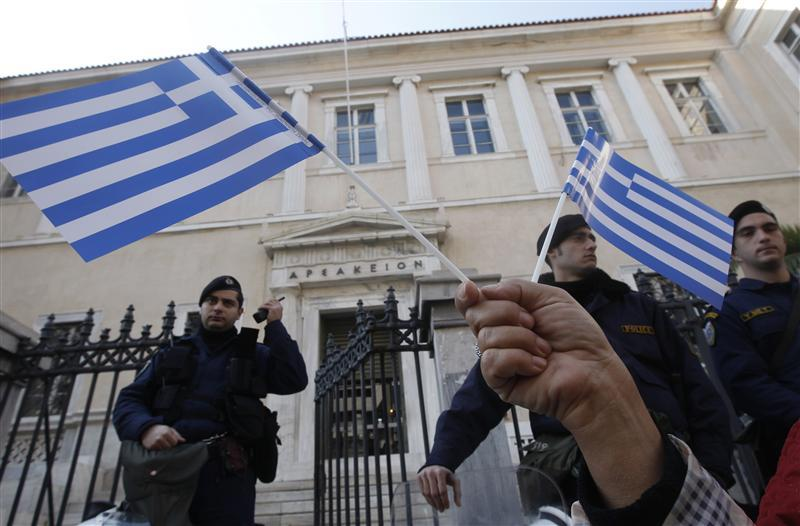 A protester holds Greek flags during a demonstration against a new property tax which has been included to the Greece's PPC bill to consumers in Athens