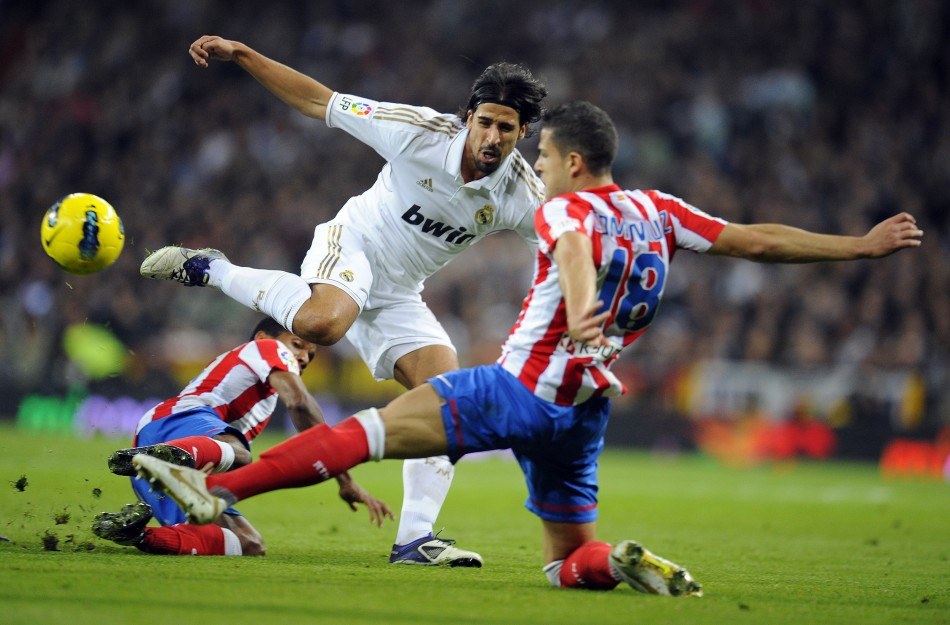 Real Madrid's Sami Khedira fights for the ball with Atletico Madrid's Alvaro Dominguez during their first division soccer match at Santiago Bernabeu stadium in Madrid