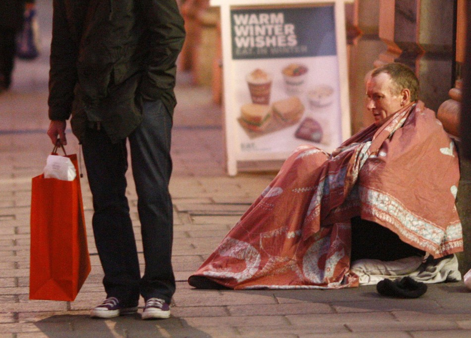 A homeless man sits outside the entrance to Green Park Tube Station on Christmas Eve in central London